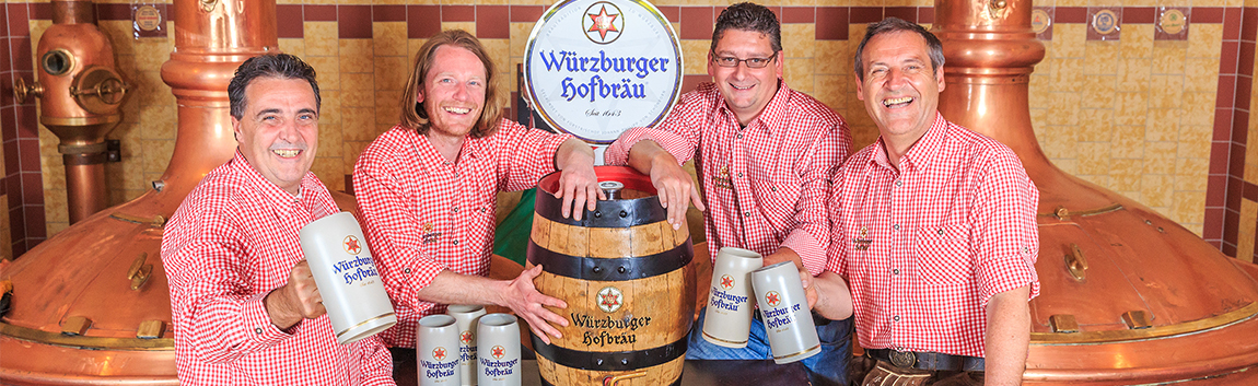 four men in a shirt with red-white chequered checker sit with a beer mug in their hands around a Würzburg Hofräu beer keg in a brewhouse