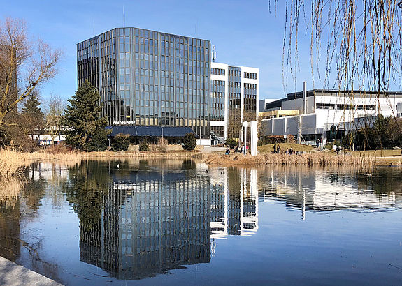 SYSKRON location Regensburg Business Park: Outside view of a mirrored office building next to a lake.