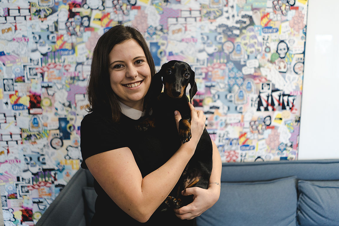 Woman with dog on her arms in front of colorful wall