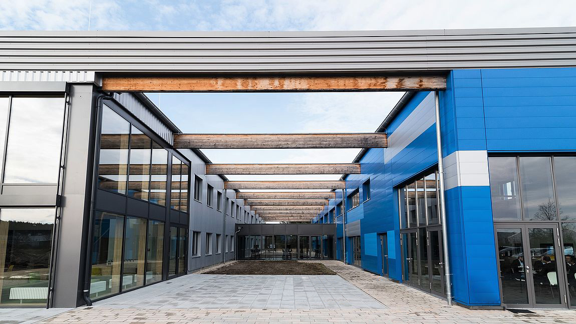 SYSKRON Headquarters Wackersdorf: Outside view of building with glass facade and beams.